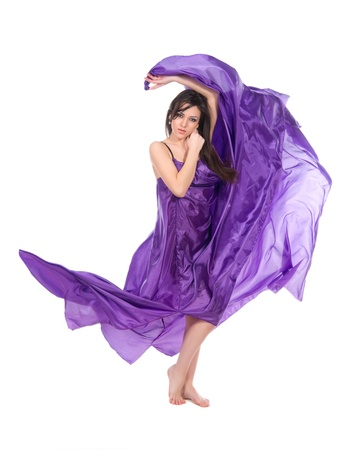 graceful girl in flying purple silk dress on a white background photo
