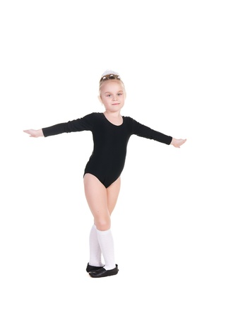 The little ballerina in a black bathing suit training on a white background