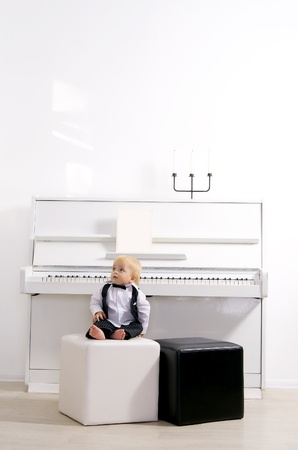 boy in a suit sitting in a concert interior reins white piano photo