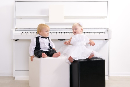 boy and girl in a suit sitting in a concert interior reins white piano photo
