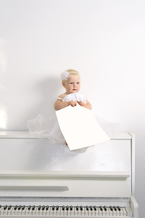 A girl in white dress sitting on a piano in the white interior photo