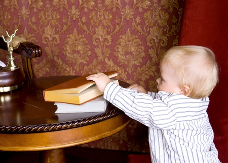 Boy runs to the books lying on a table on a background of vintage wallpaper Stock Photo - 13156662