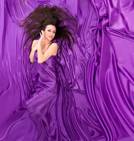 beautiful girl with long dark hair lying against a background of purple silk photo