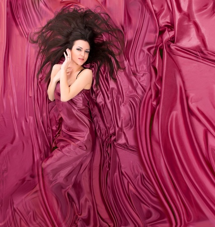 beautiful girl with long dark hair lying against a background of silk photo