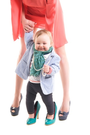 mother holding the hand of a little daughter, both dressed in fashionable clothes and wore shoes with heels photo