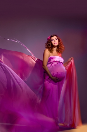 beautiful pregnant woman in a pink fabric flying, shooting mixed light photo