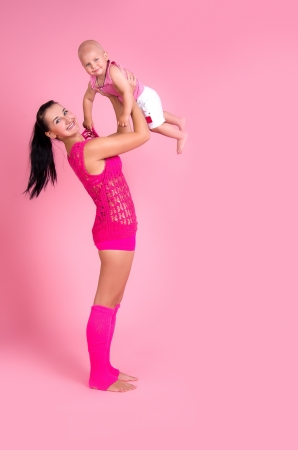 Mother throws baby up on a pink background photo