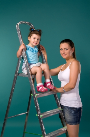 Mom stands near the ladder, on which sits a girl in the turquoise background in studio photo