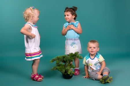 Three children playing on a turquoise background in studio photo