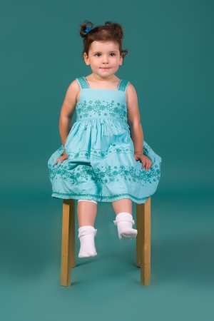 Little girl in blue dress, sitting on a chair, turquoise background in studio