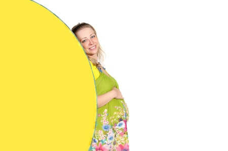 pregnant woman looks out a yellow fan isolated on white background photo