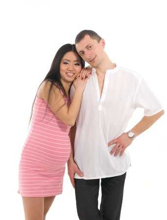 Pregnant couple Caucasoid father, mother asian, isolated on white background photo