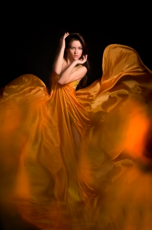 beautiful girl in the orange dress from flying fabric on a black background Stock Photo - 14109064