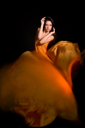 beautiful girl in the orange dress from flying fabric on a black background Stock Photo
