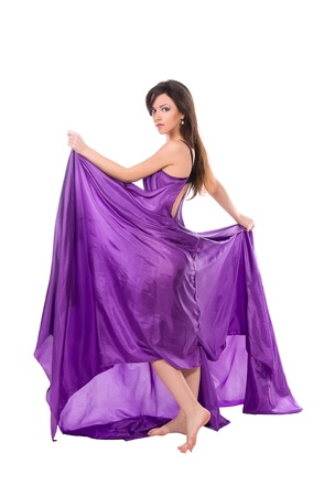 graceful girl in flying purple silk dress, isolated on a white background photo