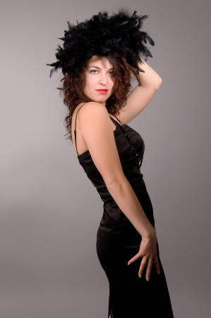 seductive beautiful girl with a black feather boa on her head