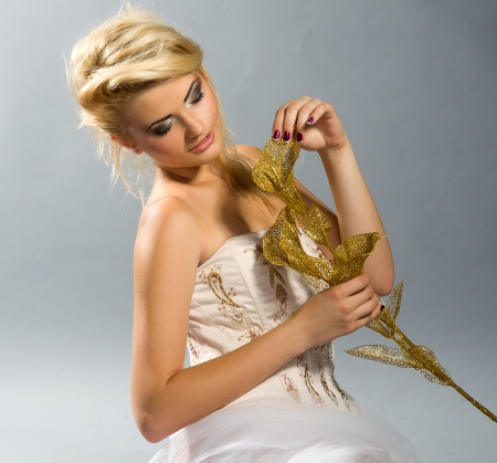 beautiful bride with blonde hair in white dress holding golden calla lilly photo