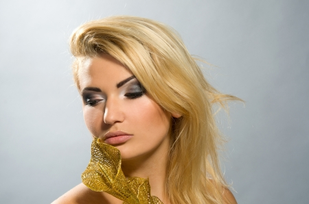 beautiful girl with blonde hair and professional makeup holding artificial golden calla lily photo