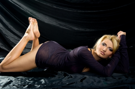 sensual blonde with a Professional make-up lies with the black satin fabrics Stock Photo