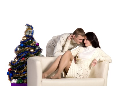 young couple at Christmas tree next to a white sofa, isolated on white background photo