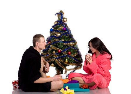 couple drinking coffee in the bath robes around dressed Christmas tree, isolated on white background photo