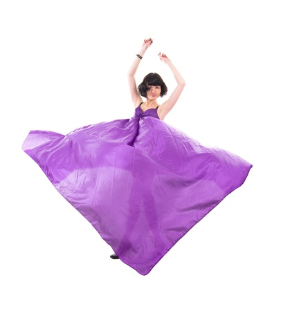 graceful girl in flying purple silk fabric, isolated on white background photo
