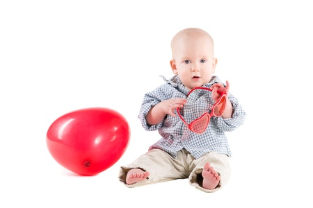 boy child is in a plaid shirt, a red balloon in the form of the heart, isolated on white background photo