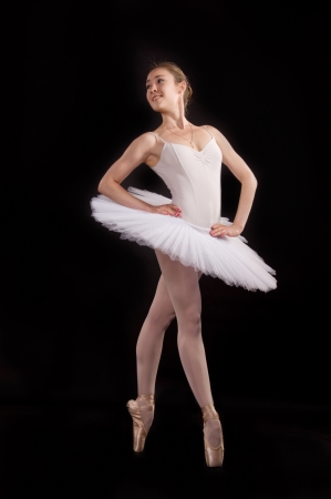 classical ballerina in a white skirt over black background photo