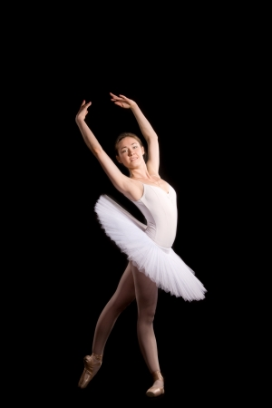 classical ballerina in a white skirt over black background Фото со стока