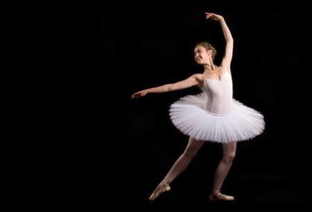 classical ballerina in a white skirt over black background Stock Photo