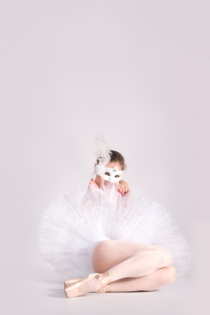 ballet dancer in a white skirt and a carnival mask  in studio photo