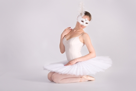 ballet dancer in a white skirt and a carnival mask. in studio photo