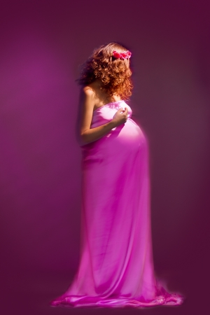 beautiful pregnant girl with flying dress train against pink and violet background photo