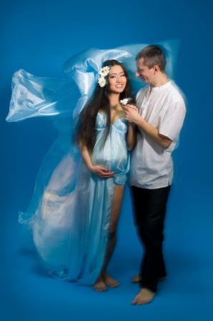 enceinte: Asian pregnant woman in a silk dress on a blue background. Shooting with a mixed light