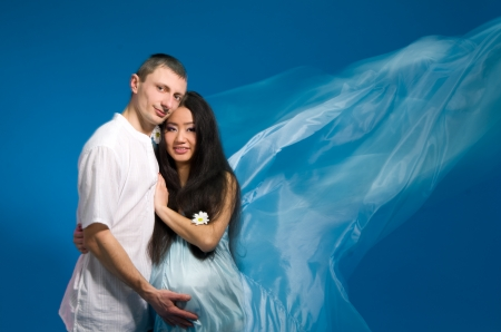 Asian pregnant woman in a silk dress on a blue background. Shooting with a mixed light Stock Photo - 14938244