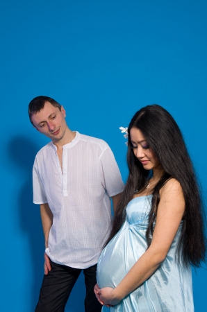 Asian pregnant woman in a silk dress on a blue background. Shooting with a mixed light photo