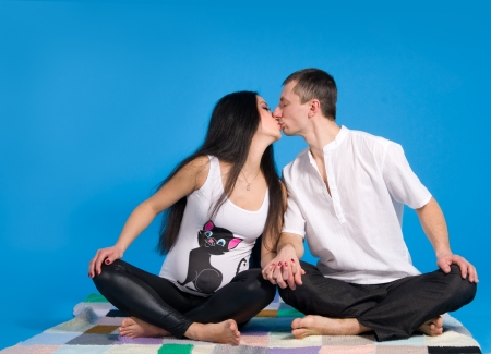 pregnant parents-in anticipation of child, on blue background in studio photo