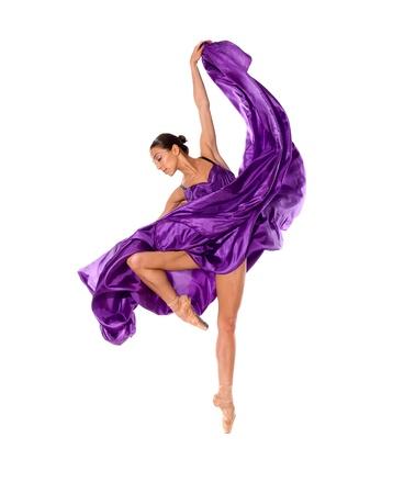 白い背景で隔離のサテンのドレスを飛んでのバレエ ダンサー