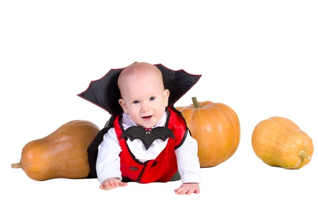 little baby boy in black halloween cloak  playing with pumpkins, isolated on a white background Stock Photo