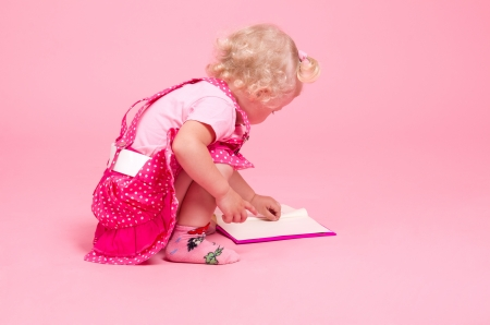 girl with enthusiasm reads the book on a pink background