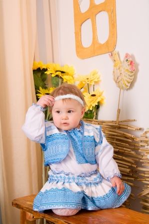 baby in national costume sitting on a bench under the Ukrainian House photo