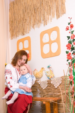 Portraite lovely family in Ukrainian national costumes. Little baby and mother photo