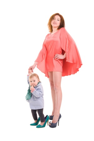 mother holding the hand of a little daughter, both dressed fashionable and wore shoes with heels, on white background photo