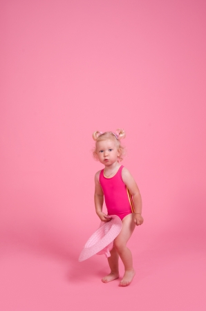 little girl with curly blond hair in a swimsuit on a pink background photo