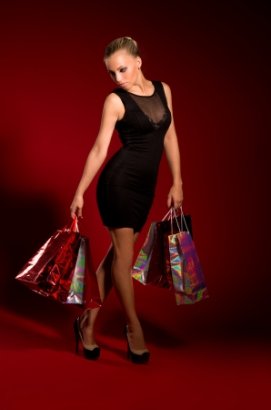 sexy girl in a black dress with bags in hands on a dark red background Stock Photo - 16512306