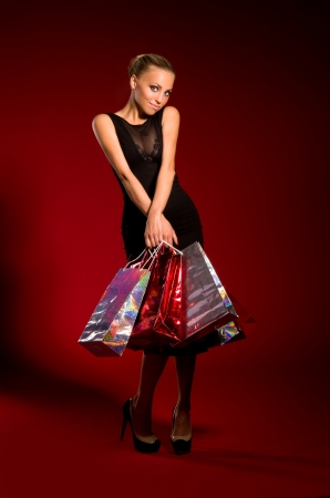 sexy girl in a black dress with bags in hands on a dark red background Stock Photo - 16512307