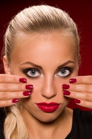 sexy girl with aggressive makeup on a dark red background photo