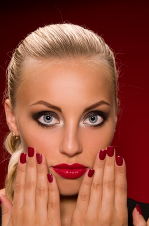 sexy girl with aggressive makeup on a dark red background