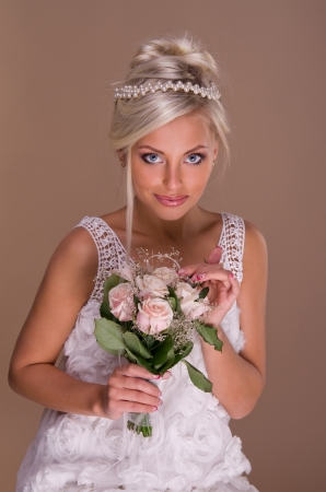 portrait of beautiful blonde bride on beige background photo