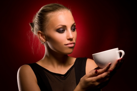 portrait of sexy girl with aggressive makeup and white cup in hand, on a black and red background photo